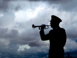 Silhouette of a man playing taps on his bugle at a veterans funeral at Medical Lake Veterans Memorial in Washington.